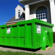 A green dumpster sitting in front of a house